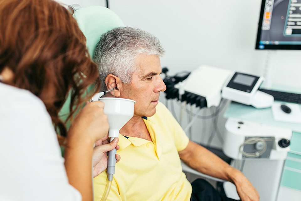 Senior man at medical clinic during ear irrigation and earwax removal