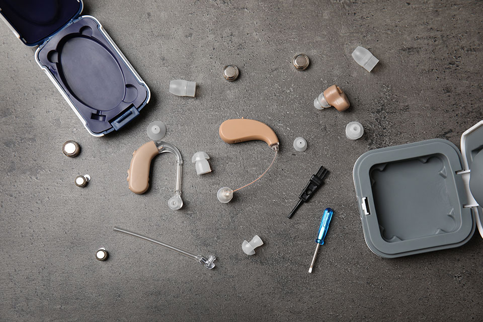 Closeup of hearing aids and accessories on grey background