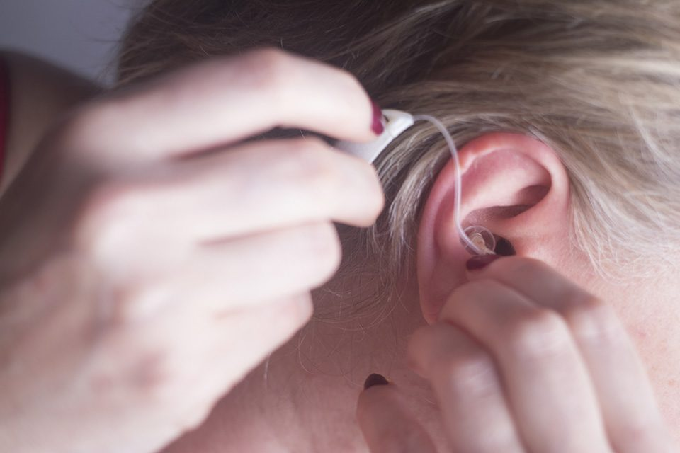 Adult woman putting hearing aid in her ear